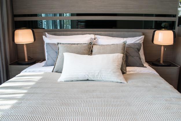 Nowoczesna sypialnia z wieloma poduszkami i dwoma światłami.