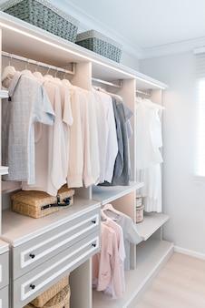 Nowoczesna szafa wewnętrzna z koszyczkiem i sukienką na półce.