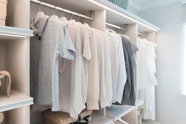 Nowoczesna szafa z koszulą i sukienką na półce.