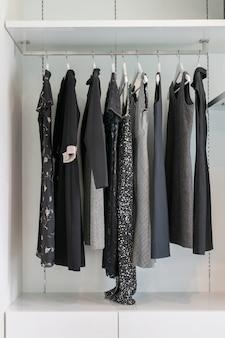 Nowoczesna szafa z rzędem czarnej sukience wisi na wieszak w szafie.
