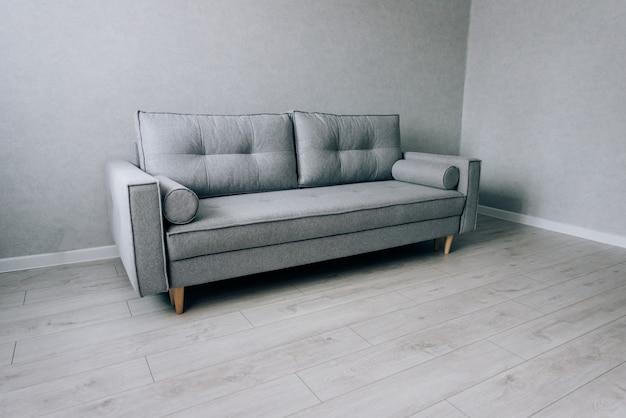 Nowoczesna szara sofa z drewnianymi nogami w pokoju