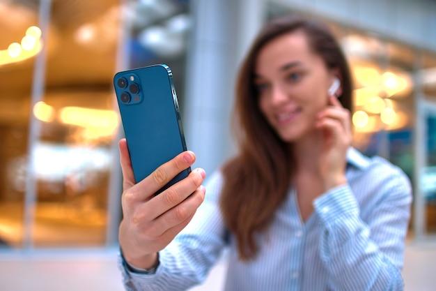 Nowoczesna szczęśliwa, dorywczo inteligentna kobieta milenialsów za pomocą smartfona do połączeń wideo i zdalnego czatu online