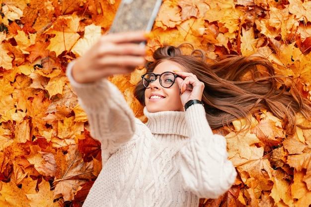 Nowoczesna szczęśliwa młoda hipster kobieta w stylowych okularach w modnym swetrze z dzianiny leży na pomarańczowych liściach w parku i robi selfie na telefonie. modna piękna dziewczyna z uśmiechem. widok z góry.