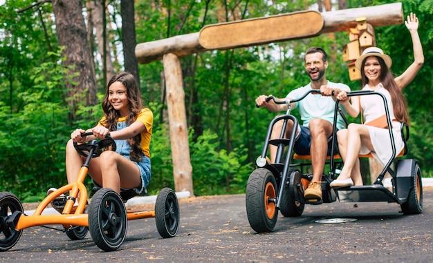 Nowoczesna szczęśliwa młoda rodzina turystów na wakacjach, jazda na rowerach i wspólna zabawa