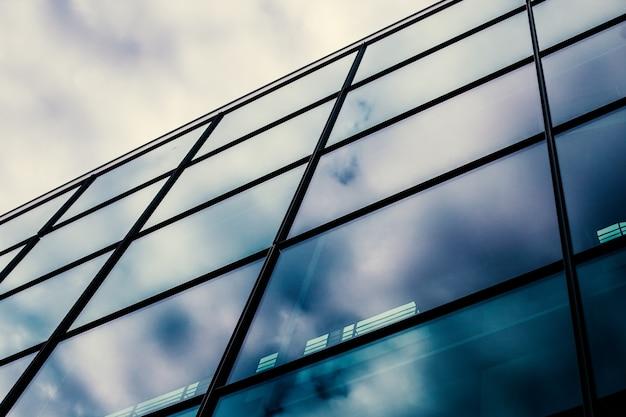 Nowoczesna szklana fasada biurowca, odbicie nieba w oknach.