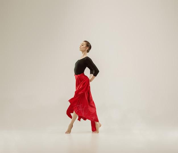 Nowoczesna tancerka baletowa ćwiczenia w całym ciele na tle białego studia. baleriny lub tancerka z jedwabnej tkaniny taniec na tle białego studia. kaukaski model na pointach