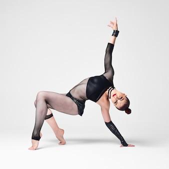 Nowoczesna tancerka jazzowa w wyrazistej tanecznej pozie. dziewczyna tancerka z jasnym makijażem i gładką fryzurą w czarnym garniturze na białym tle.