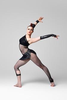 Nowoczesna tancerka jazzowa w wyrazistej tanecznej pozie. tancerka z jasnym makijażem i gładką fryzurą w czarnym garniturze