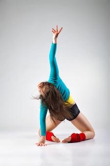 Nowoczesna tancerka pozuje na szarym tle studio we mgle