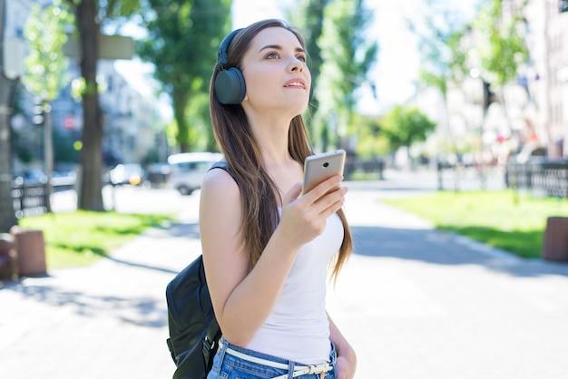 Nowoczesna technologia gadżet edukacja urządzenie studiuje koncepcję pokolenia. portret wesoły zamyślony marzycielski dama trzyma za pomocą użytkownika komórkowego w rękach trzymając czarny plecak miasto park
