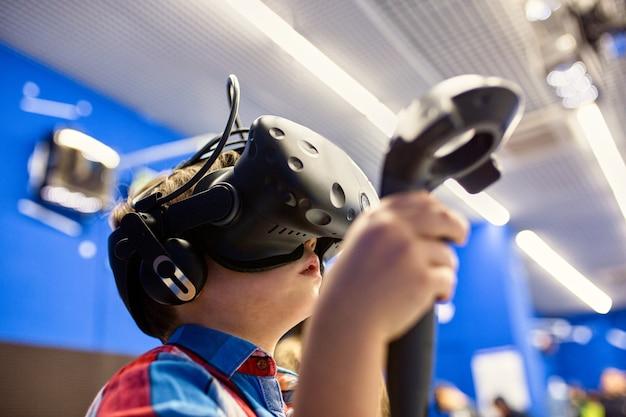 Nowoczesna technologia, gry i koncepcja ludzi - chłopiec w wirtualnej rzeczywistości zestaw słuchawkowy lub okulary 3d, grając w grę wideo w centrum gier