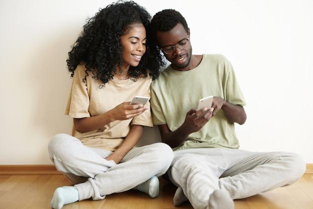 Nowoczesna technologia i komunikacja. atrakcyjny afrykański mężczyzna w okularach przedstawiający jego dziewczynie coś śmiesznego ze stylową fryzurą na telefonie komórkowym