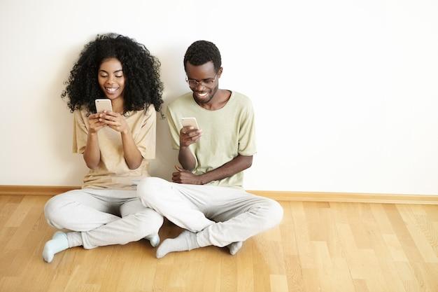 Nowoczesna technologia, ludzie i koncepcja komunikacji. niedbale ubrane, młode, ciemnoskóre małżeństwo siedzi na drewnianej podłodze ze skrzyżowanymi nogami i surfuje po internecie