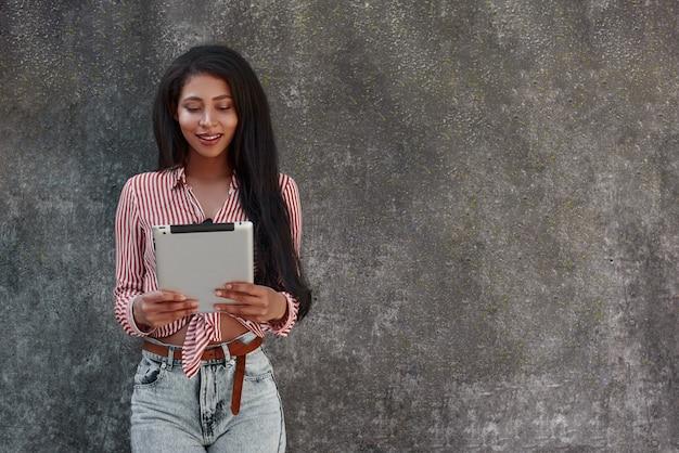 Nowoczesna technologia młoda brunetka dziewczyna stojąca na szarej ścianie, robiąca zdjęcie na cyfrowym tablecie z uśmiechem