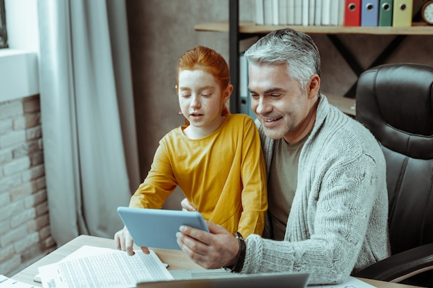 Nowoczesna technologia. pozytywnie wesoły mężczyzna patrzący na ekran tabletu, pokazujący go swojej córce