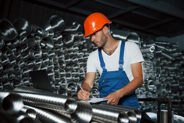 Nowoczesna technologia przemysłowa. mężczyzna w mundurze pracuje nad produkcją.