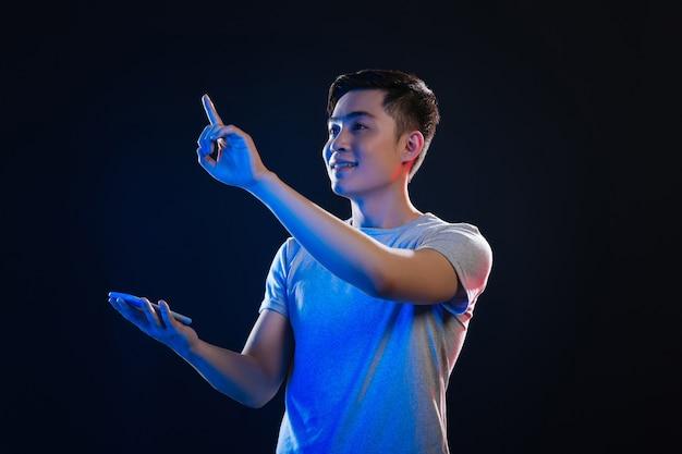 Nowoczesna technologia. radosny azjatycki mężczyzna patrząc na ekran sensoryczny, trzymając urządzenie cyfrowe