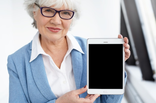 Nowoczesna technologia, starzenie się i koncepcja komunikacji online. atrakcyjny szczęśliwy dojrzały sześćdziesięcioletni bizneswoman w eleganckich okularach uśmiecha się cyfrowy tablet z pustym ekranem i trzyma