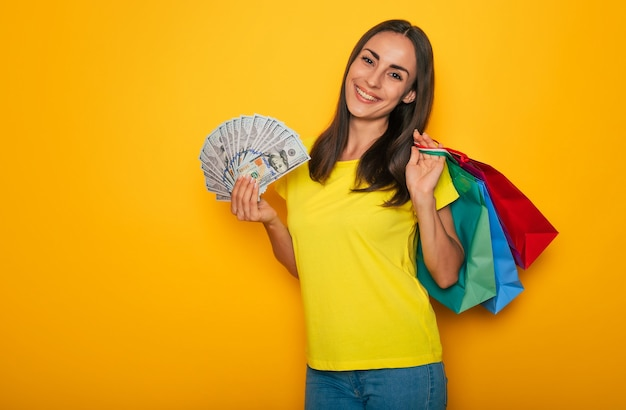Nowoczesna urocza uśmiechnięta młoda kobieta z torbami na zakupy i dolarami w dłoniach pozuje na żółtej ścianie