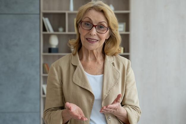 Nowoczesna uśmiechnięta starsza kobieta w okularach, która prowadzi wideorozmowę, patrząc w kamerę online