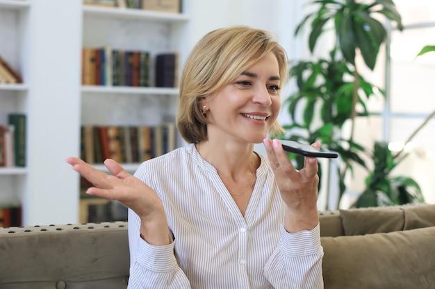 Nowoczesna wesoła kobieta w średnim wieku siedzieć w domu na kanapie trzymać smartphone rozmawiać na głośniku, za pomocą wirtualnego cyfrowego asystenta głosowego.