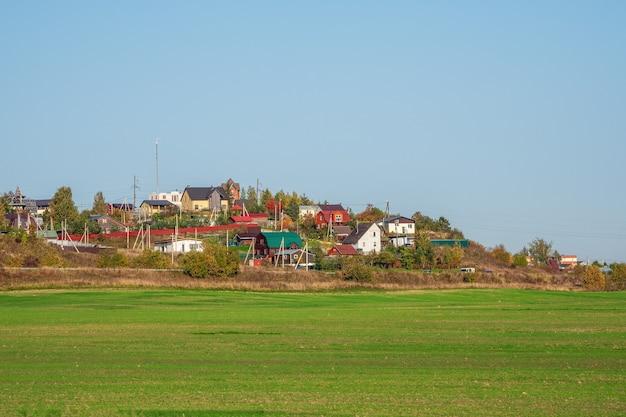 Nowoczesna wioska z domkami w zielonym polu. rosja.