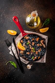 Nowoczesna włoska kolacja, dania kuchni śródziemnomorskiej, spaghetti z atramentem z czarnego mątwy z owocami morza