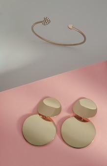 Nowoczesna złota biżuteria na białym i różowym tle