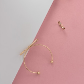Nowoczesna złota bransoletka i pierścionek na białej i różowej powierzchni