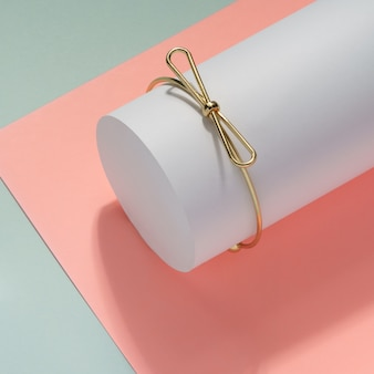 Nowoczesna złota bransoletka w kształcie łuku na białym cylindrze