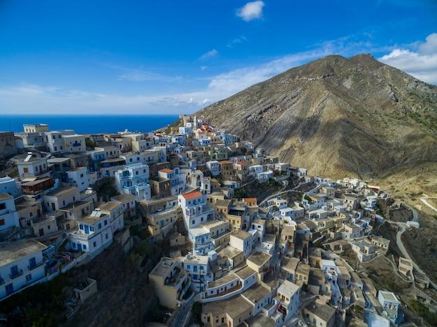 Nowoczesne białe budynki na karpathos otoczone górami i morzem