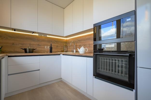 Nowoczesne białe i beżowe drewniane wnętrze kuchni