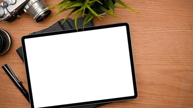 Nowoczesne biurko fotografa z makietą tabletu graficznego do montażu na drewnianym stole widok z góry