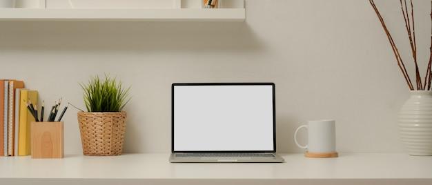 Nowoczesne biuro domowe z makietą laptopa, filiżanką kawy, papeterią, książkami i dekoracjami na białym stole