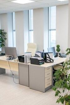 Nowoczesne biuro z biurkami, komputerami i zapasami podczas przerwy
