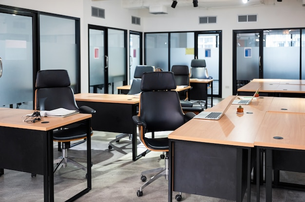 Nowoczesne biuro z biurkiem, krzesłem, laptopem tymczasowo zamknięte z powodu rządowych środków ochronnych podczas pandemii wirusa