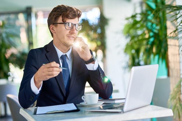 Nowoczesne biznesmen mówiąc przez telefon w świetle słonecznym