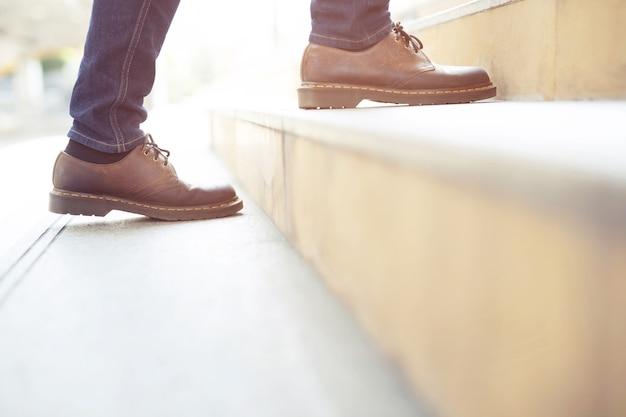 Nowoczesne biznesmen pracy zbliżenie nogi chodzenie po schodach w nowoczesnym mieście. w godzinach szczytu do pracy w biurze w pośpiechu.