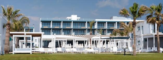 Nowoczesne budynki hotelowe nad brzegiem morza z palmami i zielonym trawnikiem