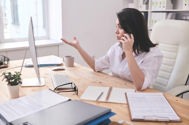 Nowoczesne businesswoman siedzi przy stole w biurze i patrząc na monitor komputera, omawiając problemy biznesowe w telefonie