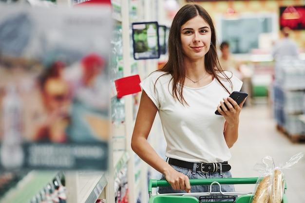 Nowoczesne centrum handlowe. kobieta kupująca w zwykłych ubraniach na rynku, szukająca produktów.