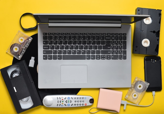 Nowoczesne cyfrowe gadżety, nośniki danych, zbędne i przestarzałe analogowe urządzenia multimedialne na żółtym tle papieru. widok z góry. leżał płasko.