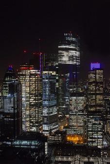 Nowoczesne drapacze chmur z oświetleniem pod nocnym niebem w londynie