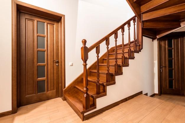 Nowoczesne drewniane schody i drzwi z brązowego dębu w nowym odnowionym wnętrzu domu