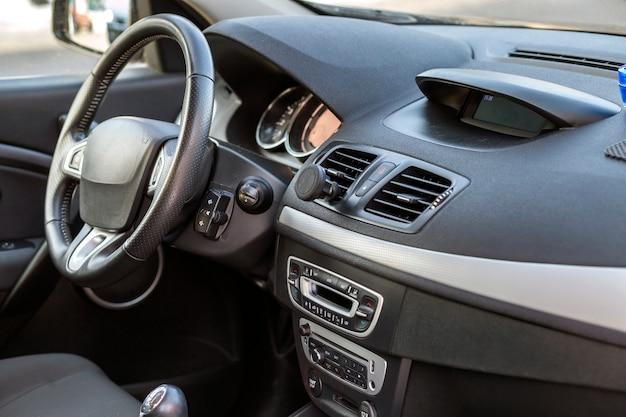 Nowoczesne drogie wnętrze samochodu. deska rozdzielcza i kierownica w kolorze czarnym. transport, projektowanie, koncepcja nowoczesnej technologii.
