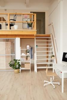 Nowoczesne dwupoziomowe wnętrze biurowe z minimalistycznym wystrojem i drewnianymi detalami