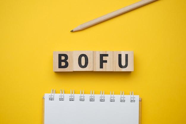 Nowoczesne hasło marketingowe - bofu dno lejka. widok z góry na drewnianym stole z bloków. widok z góry.