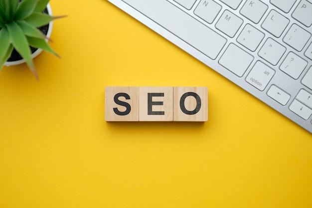 Nowoczesne hasło marketingowe seo - optymalizacja wyszukiwarek. widok z góry na drewnianym stole z bloków. widok z góry.