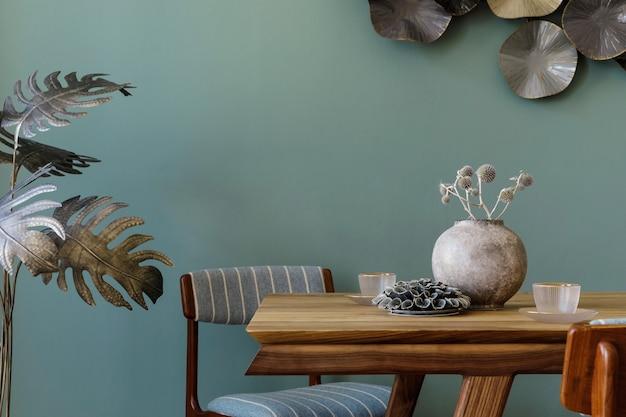 Nowoczesne i stylowe wnętrze jadalni z drewnianym stołem glamour, eleganckimi krzesłami, drewnianym parkietem i designerską dekoracją. zielone tło ściany. szablon. wystrój domu.
