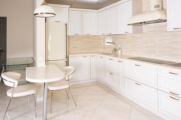 Nowoczesne, jasne, czyste wnętrze kuchni w luksusowym domu. projektowanie wnętrz z elementami klasycznymi lub vintage. praktyczna i dobrze wyposażona kuchnia.